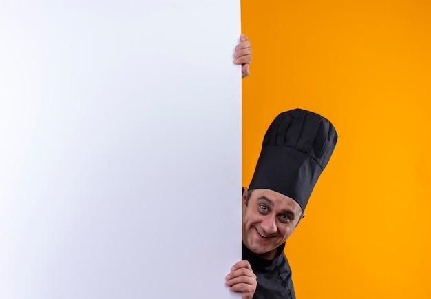 Cozinheiro de meia-idade sorridente com uniforme de chef segurando uma parede branca sobre fundo amarelo com espaço de cópia Foto gratuita