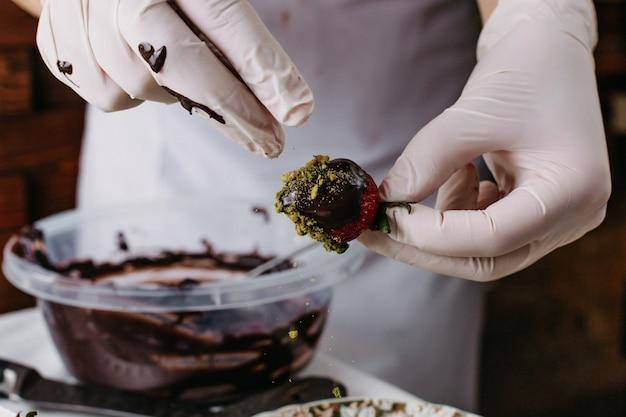 Cozinheiro de morango choco mergulhando morango vermelho dentro de chocolate Foto gratuita