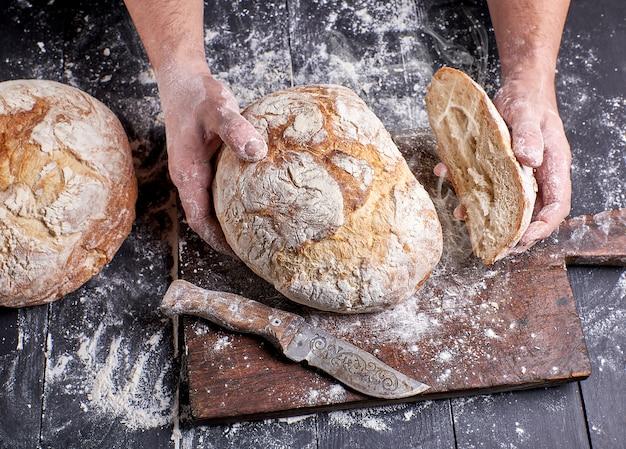 Cozinheiro, em, um, uniforme preto, segurando, fresco, quente, assado, redondo, pão Foto Premium