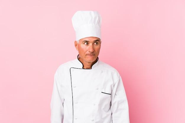 Cozinheiro envelhecido médio homem isolado confuso, sente-se duvidoso e inseguro. Foto Premium