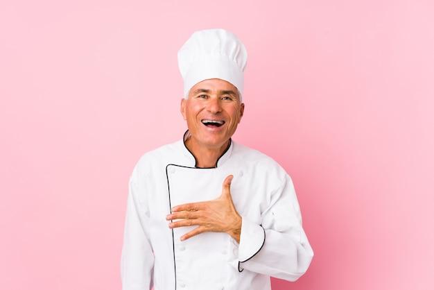 Cozinheiro envelhecido médio homem isolado ri alto, mantendo a mão no peito. Foto Premium