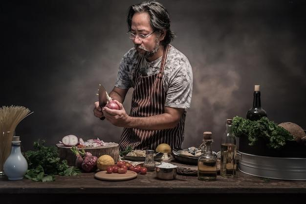 Cozinheiro farpado considerável do cheef que prepara o espaguete em uma cozinha. Foto Premium