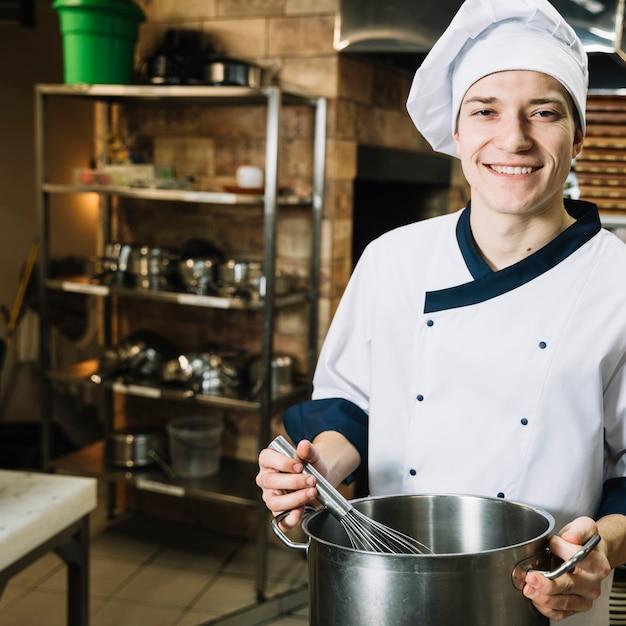 Cozinheiro feliz chicoteando algo na panela com batedor Foto gratuita