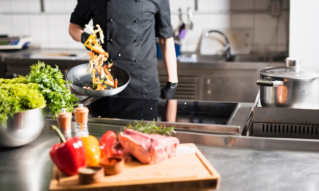 Cozinheiro, legumes jogando, em, frigideira Foto gratuita