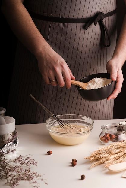 Cozinheiro masculino adicionando farinha na tigela de mistura Foto gratuita