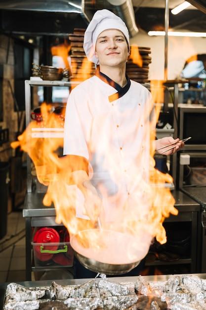 Cozinheiro masculino em branco segurando a panela em chamas na mão Foto gratuita