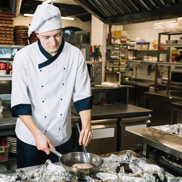 Cozinheiro masculino, fritar a carne na panela no fogão Foto gratuita