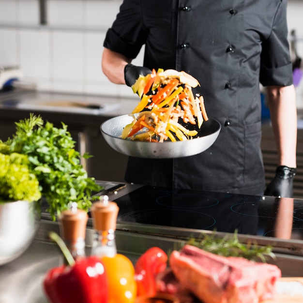 Cozinheiro masculino, jogando legumes na frigideira Foto gratuita