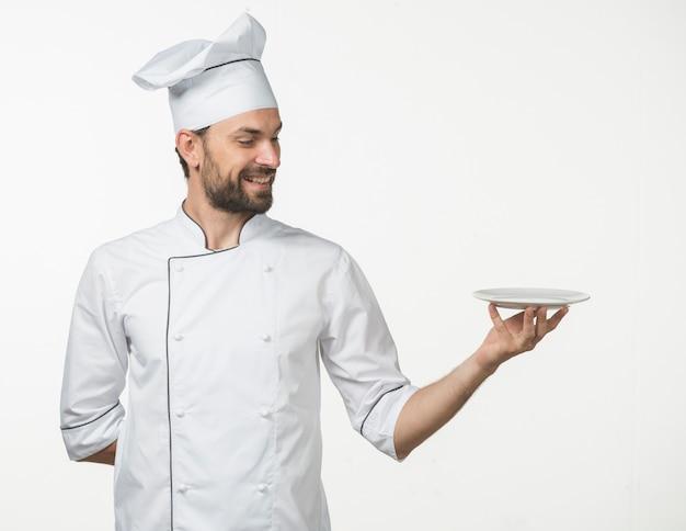 Cozinheiro masculino profissional no uniforme branco do cozinheiro chefe que apresenta o prato no fundo branco Foto gratuita