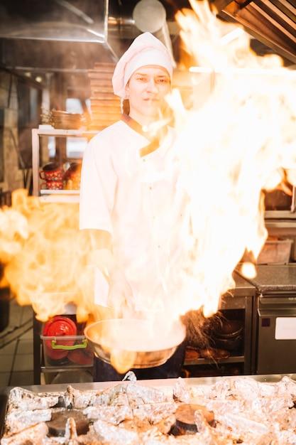 Cozinheiro masculino, segurando a panela em chamas na mão Foto gratuita