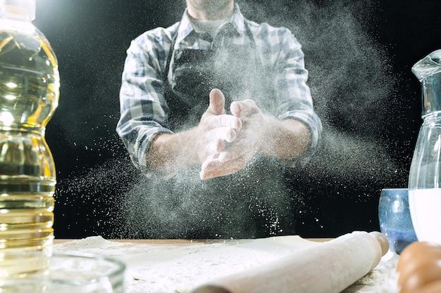 Cozinheiro profissional polvilha a massa com farinha Foto gratuita