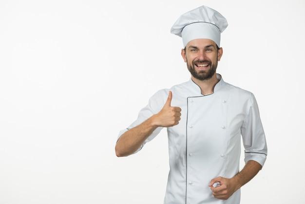 Cozinheiro profissional sorridente, mostrando o polegar para cima sinal contra o pano de fundo branco Foto gratuita