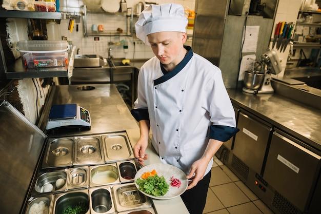 Cozinheiro, segurando, prato, com, ingredientes, em, mãos Foto gratuita