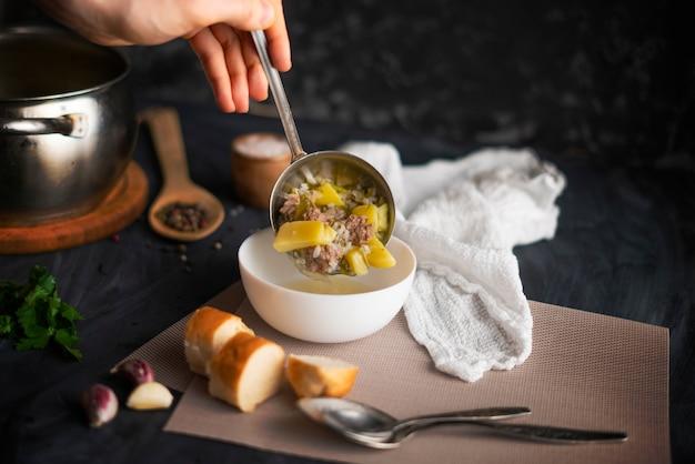 Cozinheiros mão derramar sopa quente fresca em uma tigela branca vazia, preparações alimentares Foto Premium