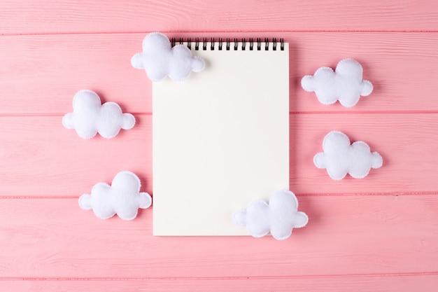 Craft nuvens brancas com notebook, copyspace em fundo rosa de madeira. brinquedos de feltro feitos à mão Foto Premium