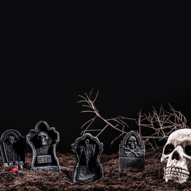 Crânio e lápides no cemitério da noite Foto gratuita