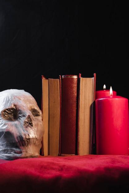 Crânio em saco de plástico com livros e velas Foto gratuita