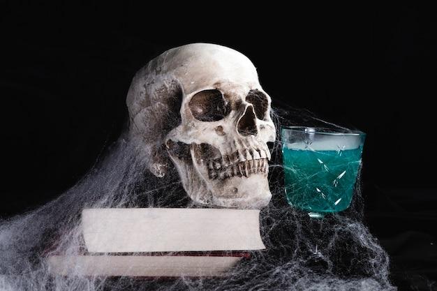Crânio humano com bebida e teia de aranha Foto gratuita