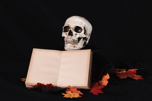 Crânio humano com livro sobre fundo preto Foto gratuita