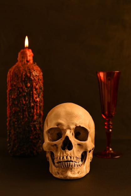 Crânio humano (réplica) no fundo de uma vela acesa Foto Premium