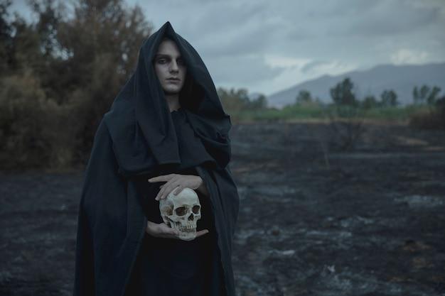 Crânio sendo realizado pelo mago masculino em roupas pretas Foto gratuita