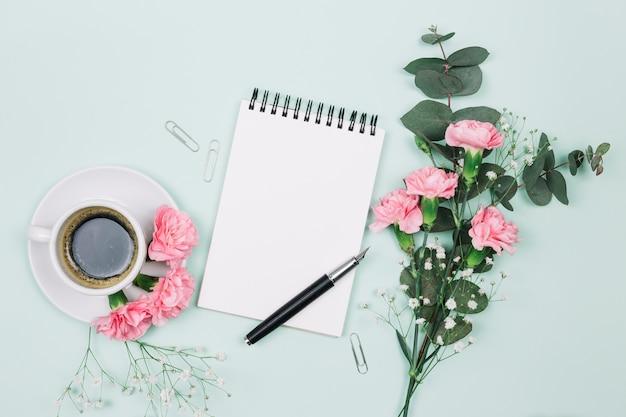 Cravos cor-de-rosa e flores de gypsophila com copo de café; bloco de notas em espiral e caneta-tinteiro em pano de fundo azul Foto gratuita