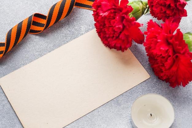 Cravos vermelhos e fita de st george em um fundo de concreto. Foto Premium