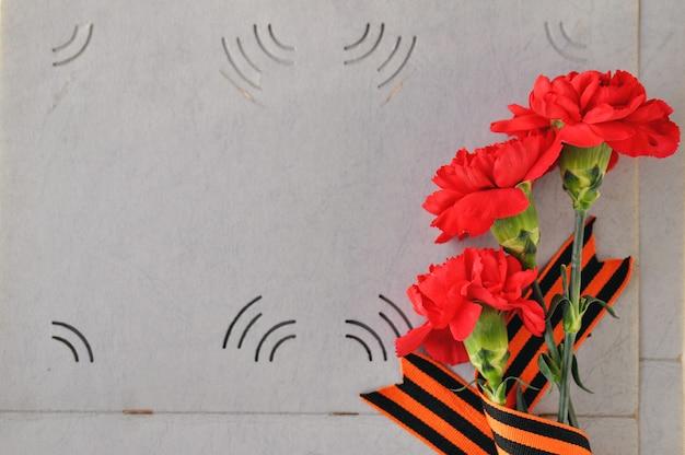 Cravos vermelhos e fita de st george no fundo de um velho álbum de fotos. dia da memória e glória militar. Foto Premium