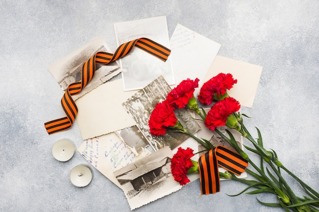 Cravos vermelhos fotos de george velho da fita em um fundo concreto. Foto Premium