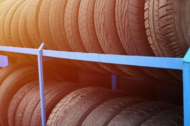 Cremalheira com variedade de pneus de carro na loja de automóvel. muitos pneus pretos. fundo de pilha de pneus. foco seletivo Foto Premium