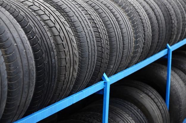 Cremalheira com variedade de pneus de carro na loja de automóvel. muitos pneus pretos. fundo de pilha de pneus Foto Premium