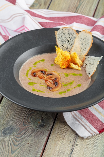 Creme de cogumelos na tigela escura. sopa cremosa caseira com cogumelos boletus fatiados. Foto Premium