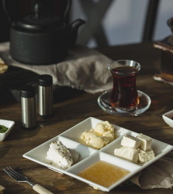 Creme de queijo, mel e manteiga com um copo de chá Foto gratuita