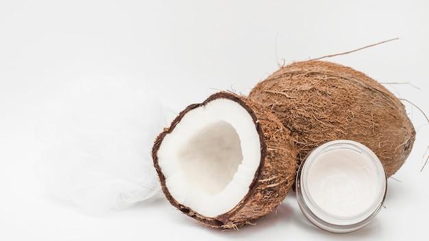 Creme hidratante; bucha e coco na superfície branca Foto gratuita