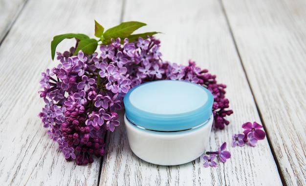 Creme hidratante e flores lilás Foto Premium