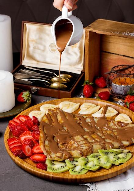 Crepe com calda de chocolate e morangos fatiados, kiwi e banana Foto gratuita