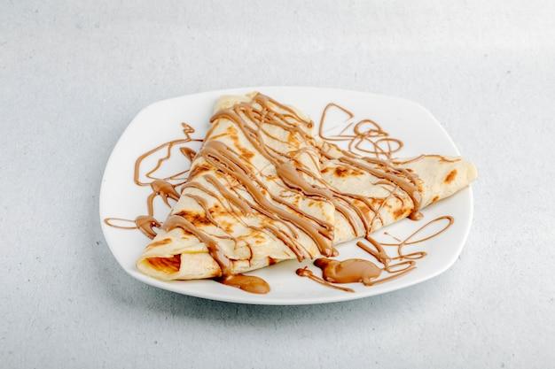 Crepe com calda de chocolate em uma placa branca em um fundo branco. Foto gratuita