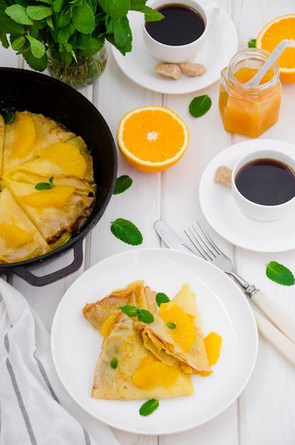 Crepe suzette com molho de laranja e uma xícara de café. café da manhã saboroso e perfumado. Foto Premium