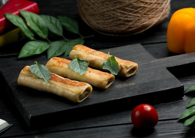 Crepes blinchik russos com folhas de orégano e tomate Foto gratuita