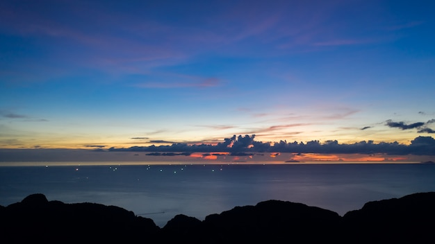 Crepúsculo, paisagem, azul, céu, e, pastel, tom, com, silueta, primeiro plano montanha, ligado, a, mar, vista aérea Foto Premium