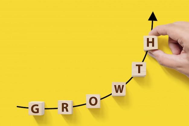 Crescimento crescente do sucesso comercial aumenta o conceito. bloco de cubo arborizado com a palavra crescimento Foto Premium