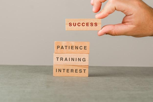 Crescimento do negócio e conceito do sucesso na opinião lateral da parede cinzenta e branca. mão colocando o bloco de madeira na torre. Foto gratuita