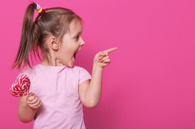 Criança abrindo a boca amplamente, olhando o outro lado com emoção, segurando coração pirulito brilhante. brincalhão alegre menina de cabelos louro passa sparetime alegremente. Foto gratuita