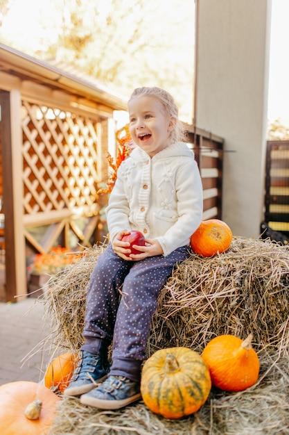 Criança adorável bebê loiro no casaco de malhas brancas, sentado no palheiro com abóboras na varanda, brincando com maçã e rindo Foto Premium