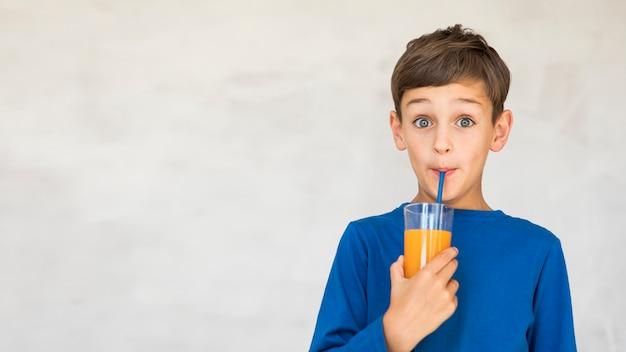 Criança adorável bebendo um pouco de suco de laranja Foto gratuita