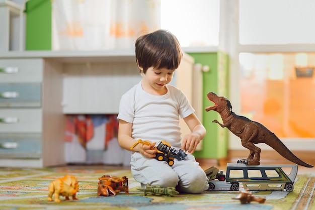 Criança adorável brincando com dinossauros em torno de muitos brinquedos em casa Foto Premium