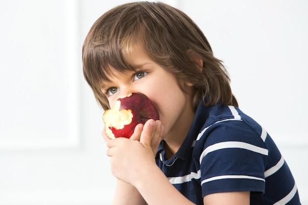 Criança adorável com maçã Foto gratuita