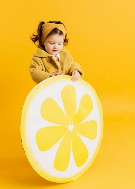 Criança adorável posando enquanto segura a decoração de fatia de limão Foto gratuita