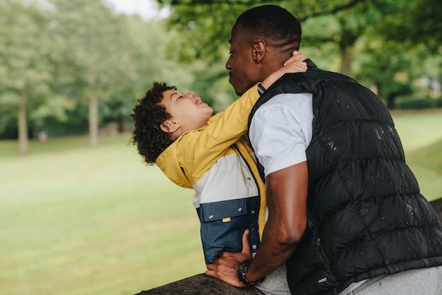 Criança afro-americana e seu pai brincando no parque Foto gratuita