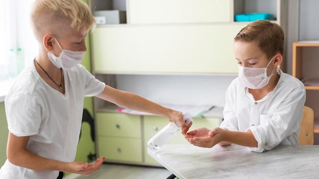 Criança ajudando seu amigo a desinfetar Foto Premium